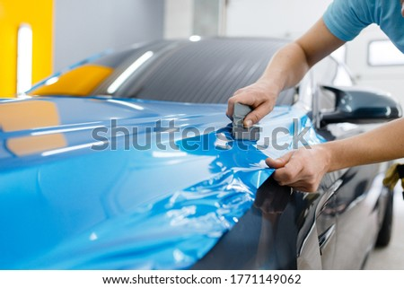 Car wrapping, mechanic with squeegee installs film Royalty-Free Stock Photo #1771149062