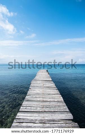 Greece - Corfu Island - Timber jetty projetcing on a calm Mediterranean Sea #1771176929