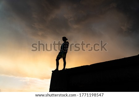 Man on the edge of cliff standing over dramatic sky during sunset .concept of thinking, meditation and concern  #1771198547