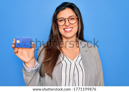 Young hispanic business woman holding credit card over blue isolated background with a happy face standing and smiling with a confident smile showing teeth