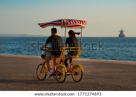 Young couple at sunset riding a four-wheeled bicycle (surrey bike) at promenade close to the sea.  Royalty-Free Stock Photo #1771274693