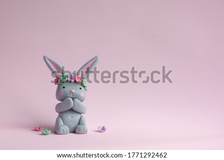 gray rabbit with a wreath of flowers on a pink background
