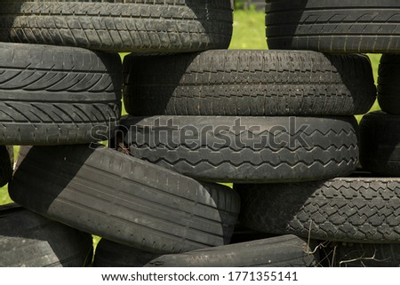 Old tires stacked to form a barricade or wall at a fairground to provide a safety feature for participants on rides and amusements #1771355141
