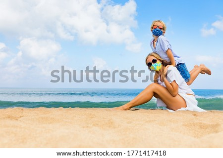 Mother, child in masks have fun on sea beach. New rules to wear cloth face covering at public places. Cancelled cruise, tour due coronavirus COVID 19. Family vacation, travel lifestyle at summer 2020 Royalty-Free Stock Photo #1771417418