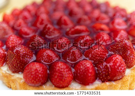 A closeup picture of a delicious strawberry cheesecake on a white plate