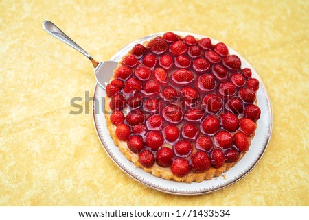 A picture of a delicious strawberry cheesecake on a white plate