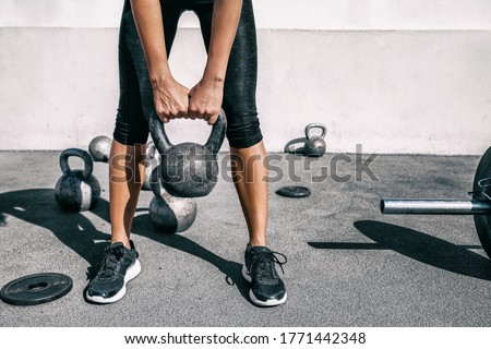 Kettlebell weightlifting athlete woman lifting weight at outdoor fitness gym. Lower body legs and feet closeup of strength training legs, glutes and back lifting free weights. #1771442348