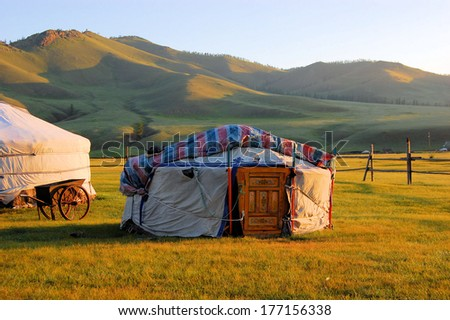 Traditional ger tent home of Mongolian nomads on the grass plains of the steppe with colorful rolling hills #177156338
