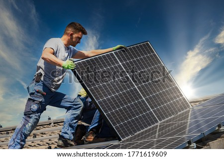 Installing solar photovoltaic panel system. Solar panel technician installing solar panels on roof. Alternative energy ecological concept. #1771619609