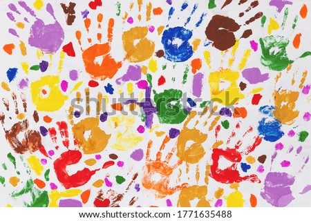 Colored prints of children's hands on a white canvas. A child's handprint on paper. Colored handprints. Many children's multi-colored handprints Royalty-Free Stock Photo #1771635488