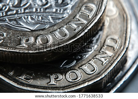 "British one Pound coins on top of each other with word ""Pound"" in a main focus. Macro. Selective focus. Concept. Royalty-Free Stock Photo #1771638533"