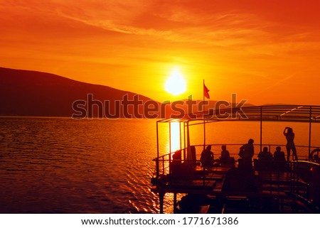 People take pictures of the sunset .Tourists sailing on a ship in the dusk . Scenery with sunset over the sea