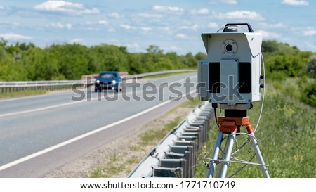 The road, the track. Radar to control the speed of cars. Installed on the side of the road. Cars are driving down the highway. Part of the photo is out of focus. Royalty-Free Stock Photo #1771710749