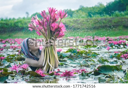 Picture with noise in low light ,Beautiful women wearing Thai dress traditional  holding lotus flower in the lotus lake countryside