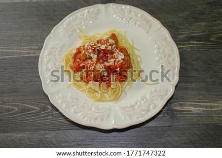 Spaghetti with meatballs topped with marinara sauce, an Italian-American dish.