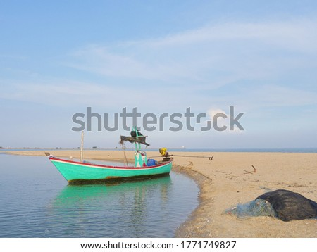 The fisherman's boat is parked, waiting for the tide to go out to fish. #1771749827