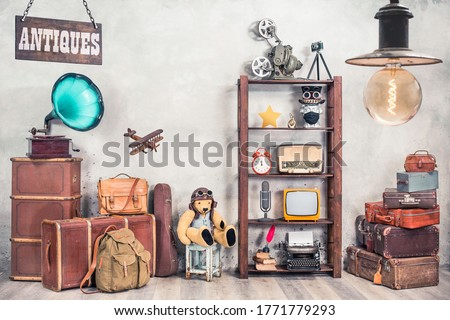 Vintage travel suitcases, backpack, old gramophone, TV, radio, mic, projector, clock, typewriter, quill, books, camera, Teddy Bear, toy plane, signboard, mask. Antiques collectibles. Retro style photo #1771779293