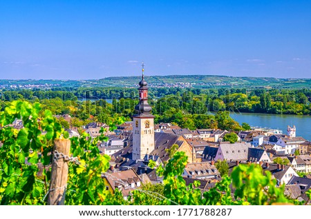 Aerial view of Rudesheim am Rhein historical town centre with clock tower spire of St. Jakobus catholic church and Rhine river, blue sky background, Rhineland-Palatinate and Hesse states, Germany #1771788287