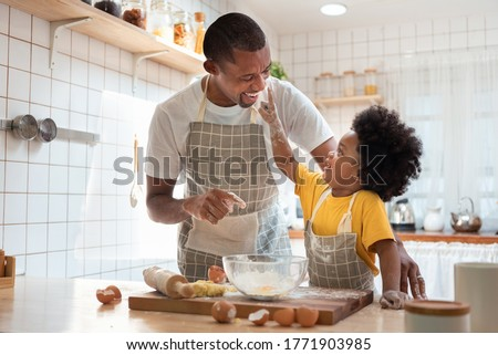 African family have fun cooking baking cake or cookie in the kitchen together, Happy smiling Black son enjoy playing and touching his father nose with finger and flour while doing bakery at home. #1771903985