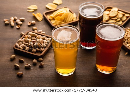 Table for company of friends. Crispy snacks and different types of beer in glasses on wooden background, close up Royalty-Free Stock Photo #1771934540
