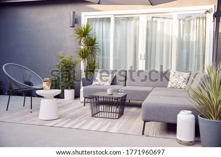 Outdoor Seating And Garden Furniture On Patio Of Contemporary Home Royalty-Free Stock Photo #1771960697