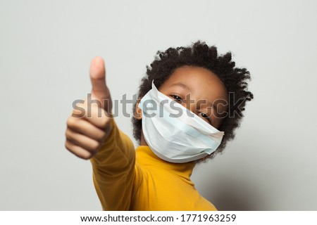 Happy African American black kid in medical protective face mask showing thumb up on white #1771963259
