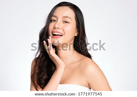 Beauty face. Smiling asian woman touching healthy skin portrait. Beautiful happy girl model with fresh glowing hydrated facial skin and natural makeup on white background, #1771977545