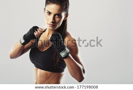 Pretty young woman wearing boxing gloves posing in combat stance looking at camera. Fit young female boxer ready for fight on grey background Royalty-Free Stock Photo #177198008