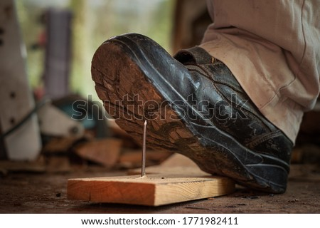 Worker in safety shoes stepping on nails on board wood In the construction area Royalty-Free Stock Photo #1771982411