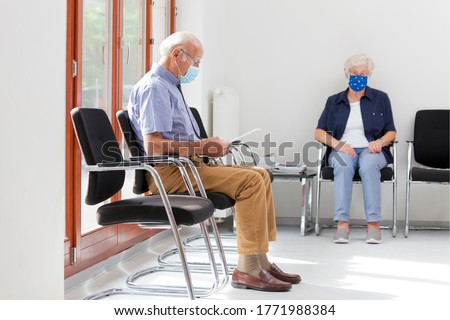 Senior woman and man sitting with face masks in a bright waiting room of  a hospital or an office #1771988384
