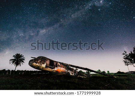 A picture of an abandoned plane under the starry sky