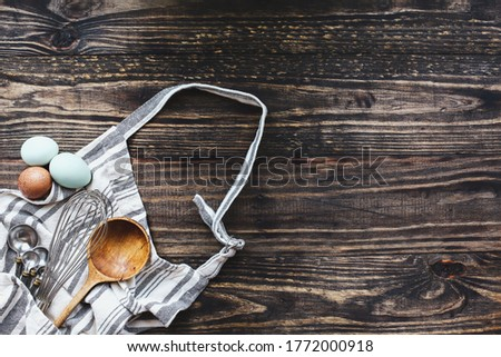 Apron with baking supplies. Whisk, measuring spoons, old wooden spoon and eggs over a dark rustic wood table background. Image shot from top view.