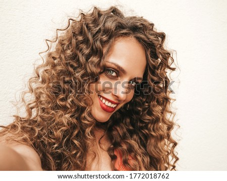Beautiful smiling model with afro curls hairstyle dressed in summer hipster clothes.Sexy carefree girl posing in the street in sunglasses.Taking selfie self portrait photos on smartphone