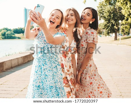 Three young beautiful smiling hipster girls in trendy summer sundress.Sexy carefree women posing on the street background. Positive models having fun and hugging.Taking selfie self portrait photos