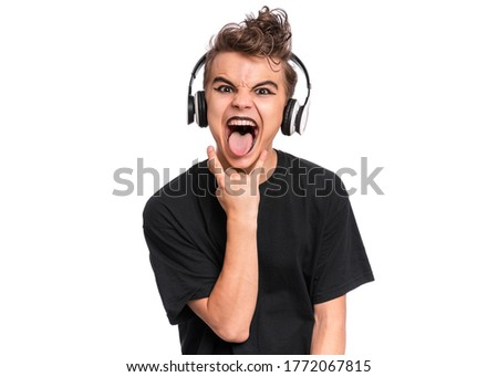 Teen boy in headphones with spooking make-up making Rock Gesture, isolated on white background. Teenager in style of punk goth dressed in black screaming and shouting, doing heavy metal rock sign.