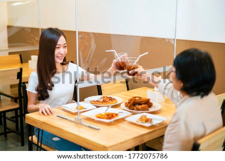 Asian beautiful female clinking a glass of water with her mother who siting separate and keep distance with table plastic shield partition in restaurant, new normal and social distancing concept Royalty-Free Stock Photo #1772075786