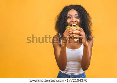 African American black beautiful young woman eating hamburger isolated on yellow background. Royalty-Free Stock Photo #1772104370