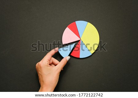 Colorful fraction circles arranged into a circle graph and hand, black background. Royalty-Free Stock Photo #1772122742