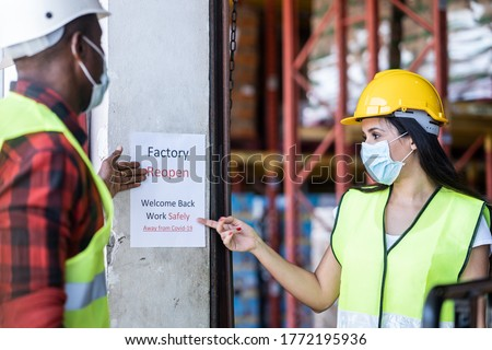 Latin woman and black man worker in warehouse factory looking at sign paper written factory reopen, welcome back due covid19 pandemic and current situation is better. They feeling happy to work again. #1772195936