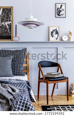 Stylish scandinavian bedroom interior with design chair, plant, mock up picture frames, book, clock, decoration, carpet, beautiful bed sheets, blanket and pillows in modern home decor.