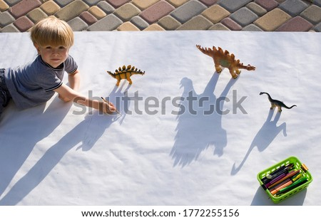 child draws with a pencil contrasting shadows from toy dinosaurs. drawing a preschooler, creative ideas for children's creativity. Interesting activities for the development of children