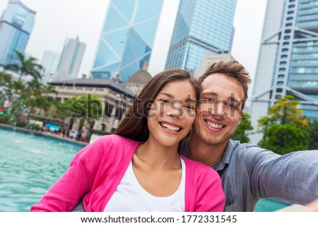 Selfie tourists couple Asian woman and Caucasian taking picture with phone in Hong Kong city, Asia travel lifestyle. Two people taking a self potrait photo.
