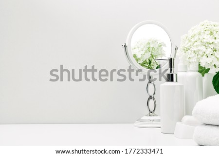 Soft light bathroom decor for advertising, design, cover, set of cosmetic bottles, white flowers, bath accessories, mirror, towel on white background. mock up, copy space