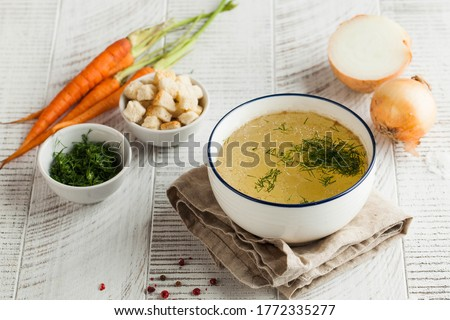 Homemade broth in a white bowl on a napkin with dill, fresh carrots and onions. concept of healthy eating. Copy space.