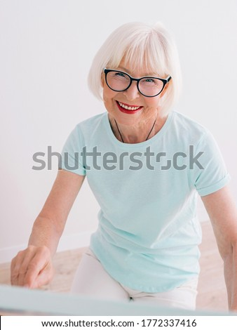 senior cheerful woman in glasses with gray hair drawing with pencil flowers in vase. Creativity, art, hobby, occupation concept #1772337416