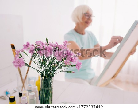 senior cheerful woman in glasses with gray hair drawing with pencil flowers in vase. Creativity, art, hobby, occupation concept #1772337419