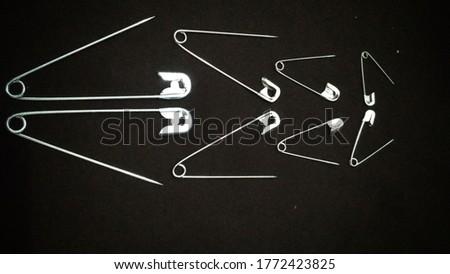 Peniti. Safety pin Isolated on black background.  Royalty-Free Stock Photo #1772423825