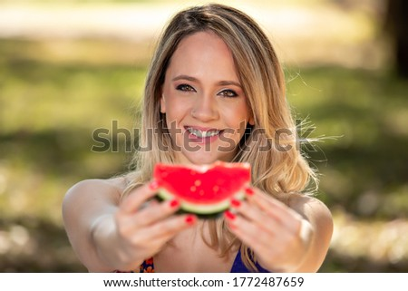 Young woman outdoors under trees in a park, happy and smiling, doing pic nic and tasting watermelon