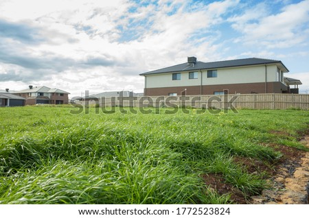 Vacant land next to some residential suburban houses. Concept of real estate development, land for sale and a new suburb, Tarneit, Melbourne, VIC Australia. Royalty-Free Stock Photo #1772523824