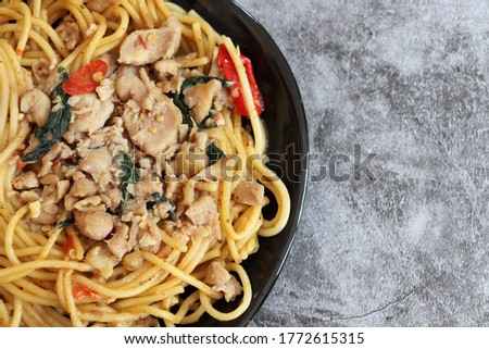 Close up picture of delicious stir-fried basil chicken spaghetti on black dish over gray background with copy space